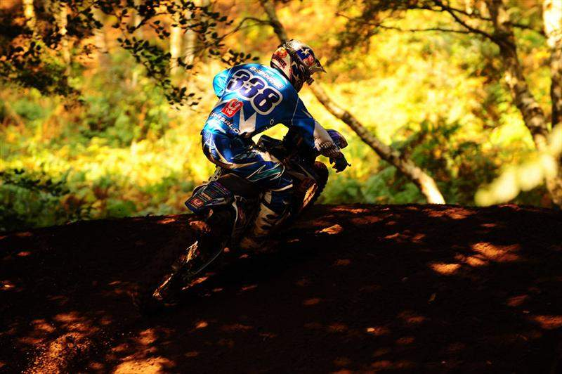Zach Osborne rides through the shade trees.