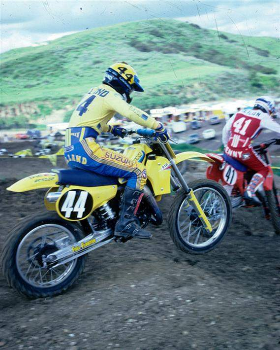 "This is a cool shot of George Holland riding what must be practice with Kenny Keylon. We know it was taken in 1982, because that was the year Keylon won the '82 St. Petersburg National wearing #41. ""The Almond Farmer,"" as Holland was known by, is riding an RM125 Full Floater, while Kenny is on a CR250."