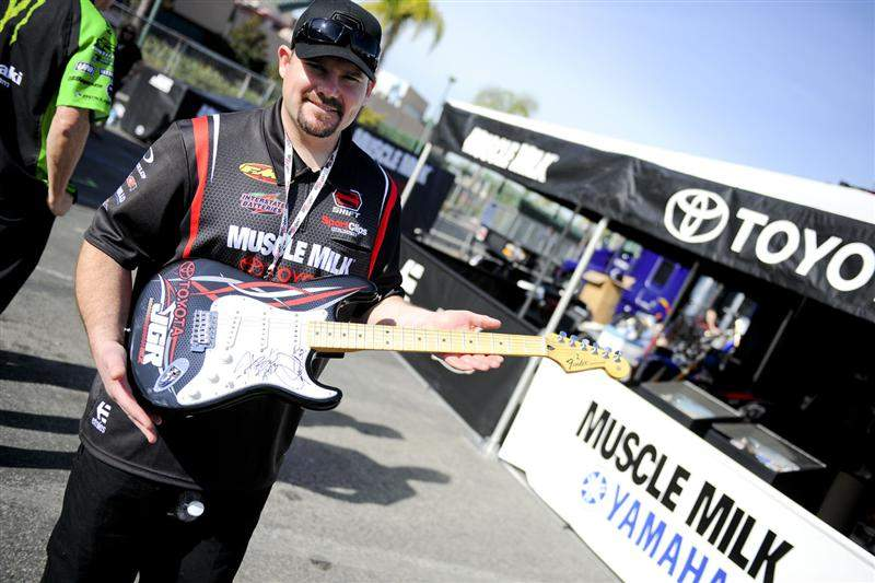 Coy Gibbs shows off the Fender Stratocaster they're giving away. It's signed by both Josh Grant and Justin Brayton.