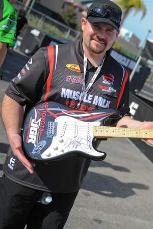 Coy Gibbs showing off a guitar his team is giving away.