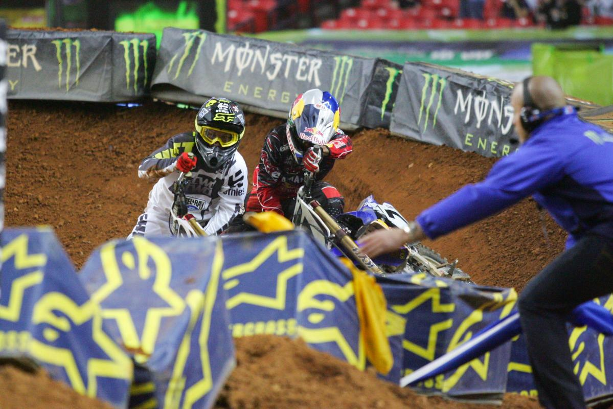 Chad Reed and James Stewart wrestle to get their bikes back up.