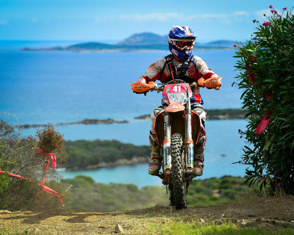 With the sparkling Mediterranean Sea in the background Kurt Caselli crests a hill during this year's Italian ISDE.