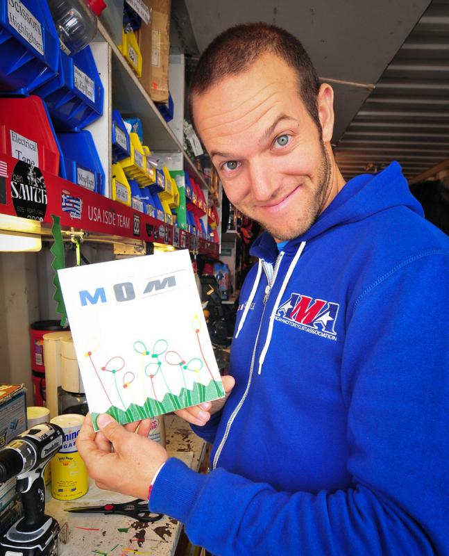 Kurt Caselli shows of a makeshift birthday card that he made for his mother's birthday during the German ISDE in 2012. The card consisted of green duct tape, zip-ties and letters cut from graphic kits.