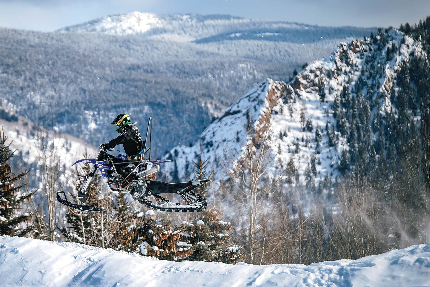 Pro motocross legend Doug Henry hovers above the Rocky Mountains on his way to an X Games gold medal in Para Snow BikeCross.